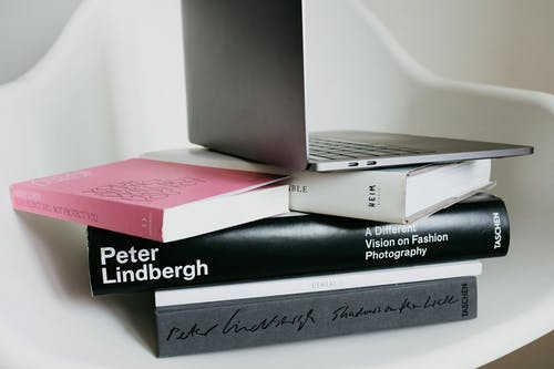 Modern laptop on top of books stacked on white chair