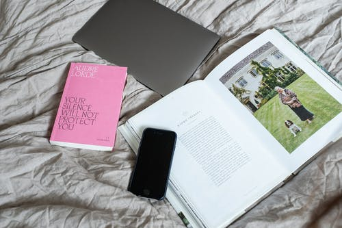 Set of book with smartphone and laptop placed on blanket on bed