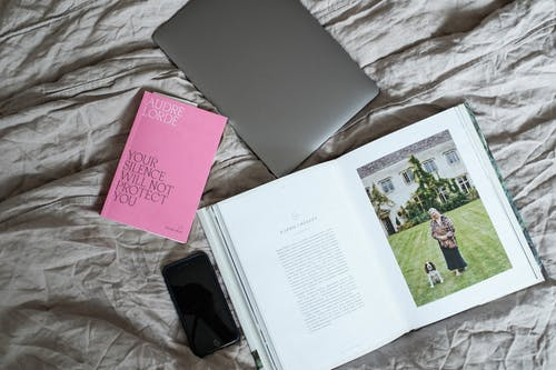 Top view of opened book with laptop and smartphone placed on soft blanket on comfortable bed in modern light bedroom