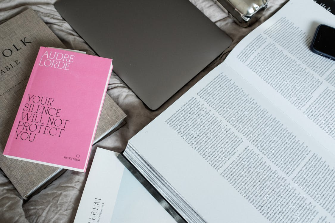 Layout of books smartphone and tablet on bed