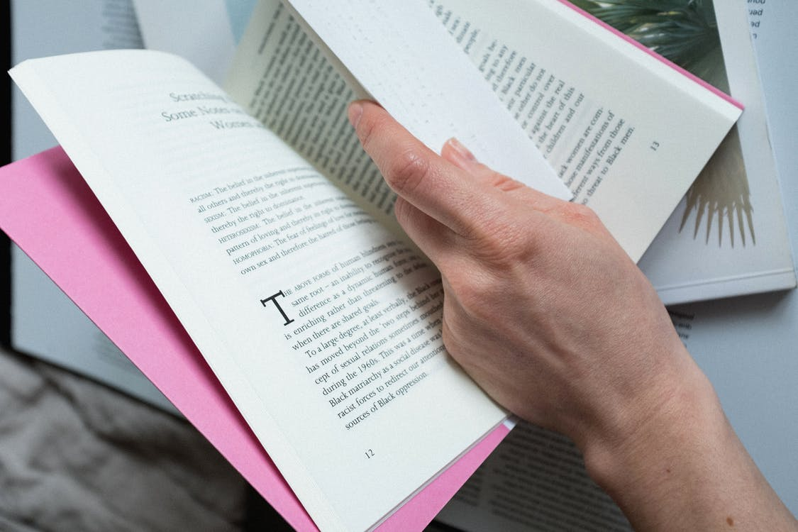 From above of crop person hand with paper reading book with pink cover on bed