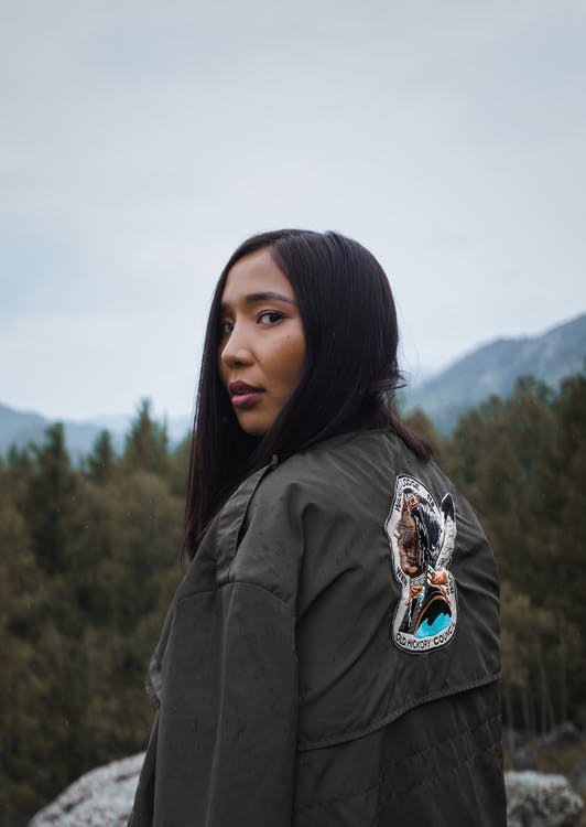 Back view of young ethnic lady with makeup in jacket with bright trendy pattern standing near rough stone and mounts with trees under sky and looking at camera over shoulder