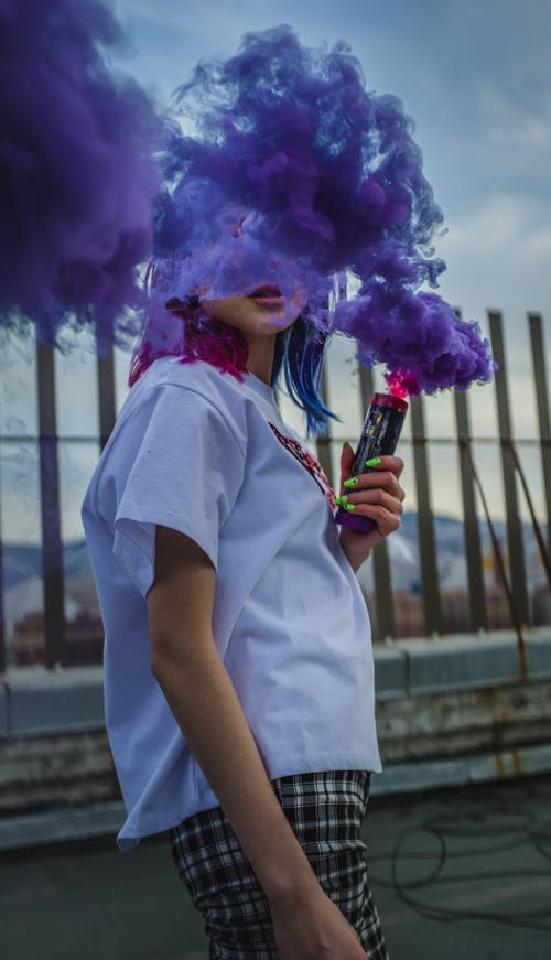 Unrecognizable woman with colored smoke bomb creating cloud effect outdoors