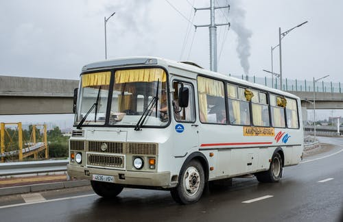Local public bus with anonymous driver and passengers windshield driving on asphalt road with marking lines near cement bridge under cloudy sky with smoke