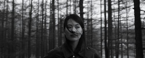 Contemplative Asian woman standing in forest