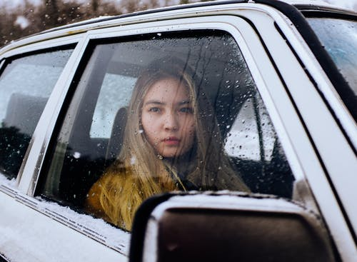 Young dreamy blond female sitting in automobile while looking away through window covered with small droplets in wintertime in daylight