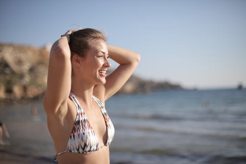 Cheerful woman sunbathing on sea beach