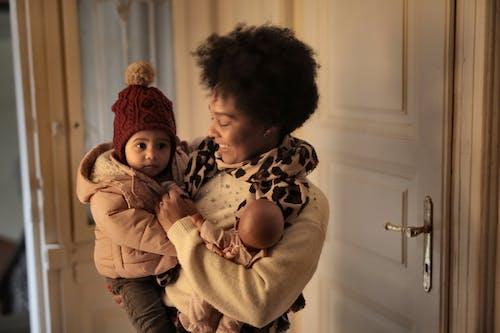 De Gelukkige Baby Van De Moederholding Op Handen