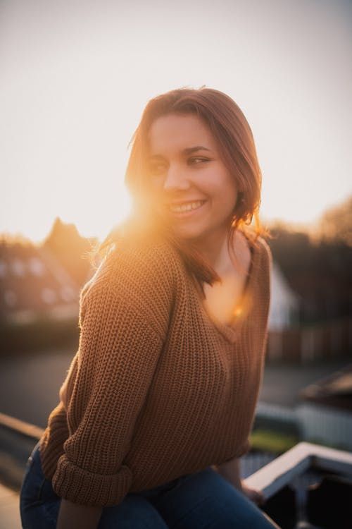 Woman in Brown Sweater Smiling During Sunset