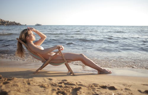 Woman in White Bikini Sitting on Brown Wooden Folding Chair on Beach