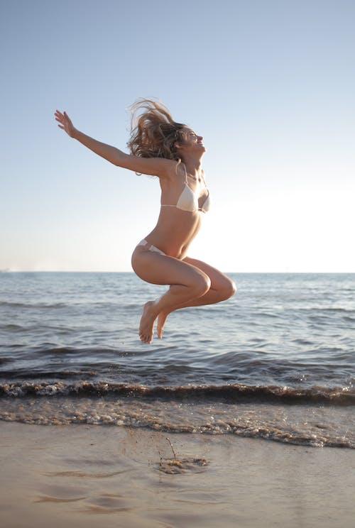 Woman In White Bikini Standing On Beach