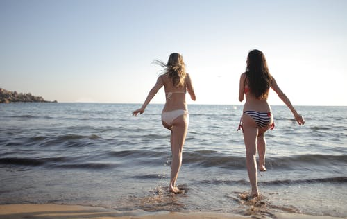 Happy women cheerfully walking into seawater
