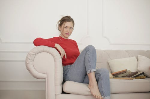 Woman In Red Long Sleeve Shirt And Denim Jeans Sitting On Sofa Chair