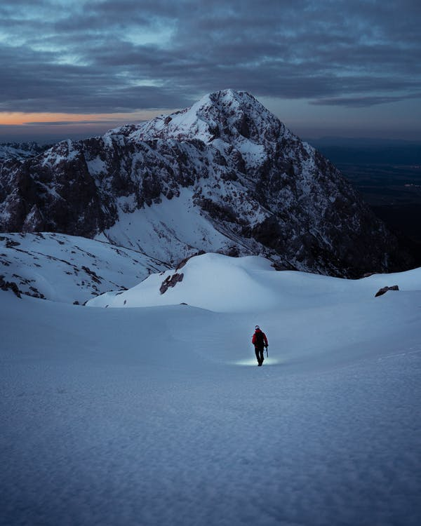 Person in Red Jacket and Black Pants Walking on Snow Covered Ground Near Mountain