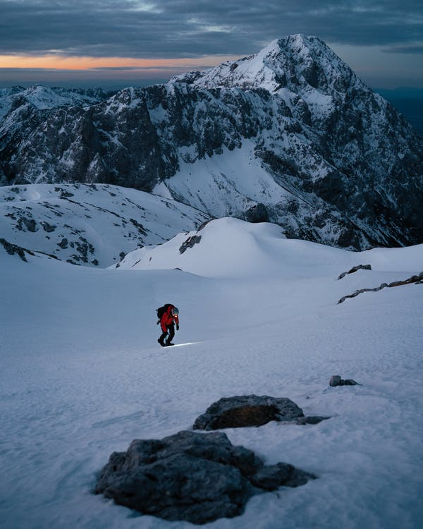 Person in Red Jacket and Black Pants Walking on Snow Covered Ground