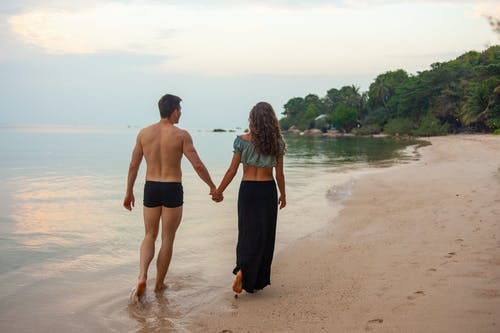 Photo of Man and Woman Holding Hands Walking on Beach