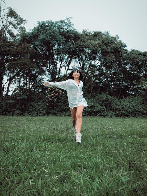 Woman in White Dress Shirt Standing on Green Grass Field