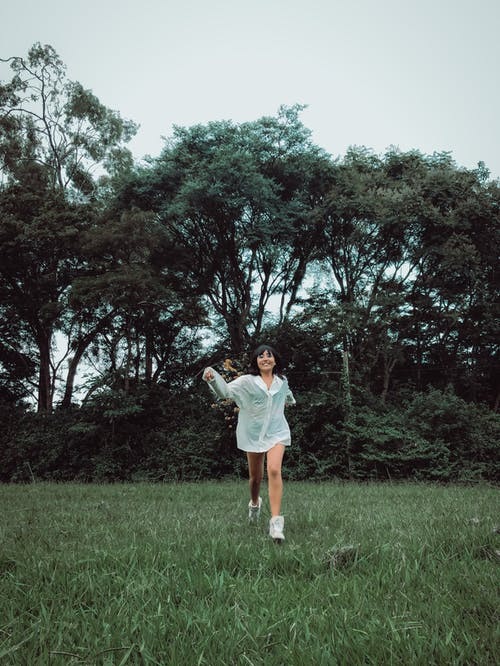 Woman in White Top Running On Grass Field