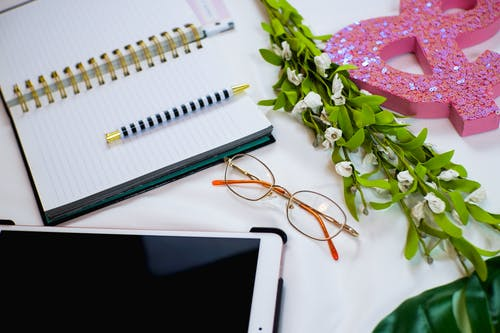 White Ipad Beside Pink and White Floral Textile
