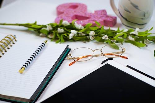 Silver Framed Eyeglasses on White Notebook