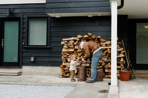 Man Showing Firewood to Little Girl