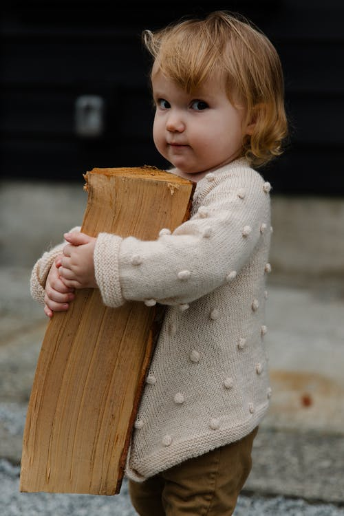 Girl in White Sweater Holding Brown Wooden Log