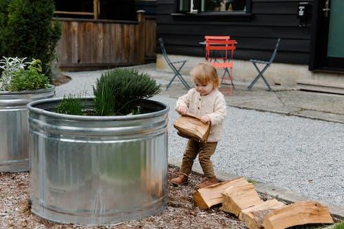 Little Girl Carrying Wooden Logs