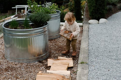 Little Girl Carrying Wooden Log