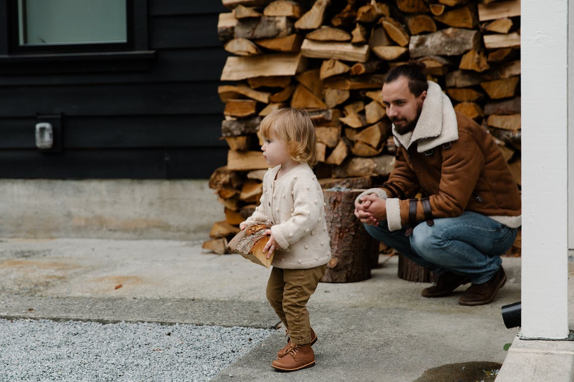 Cheerful man smiling while sitting and looking at child while playing with firewood in yard and having fun together during weekend