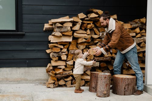 Man Showing Wood to Little Girl