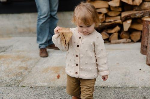 Little girl walking with firewood in yard