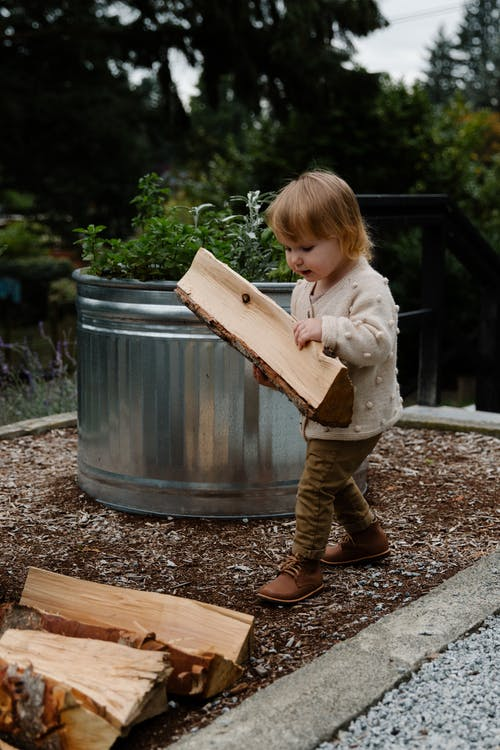 Little girl building with firewood in garden