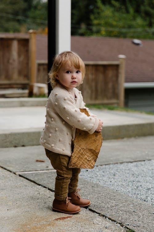 Little Kid Holding Wooden Log