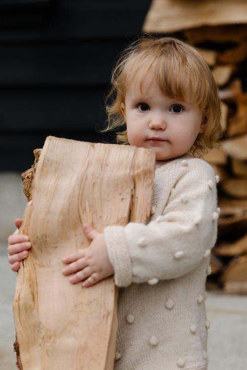 Little girl hugging firewood in yard