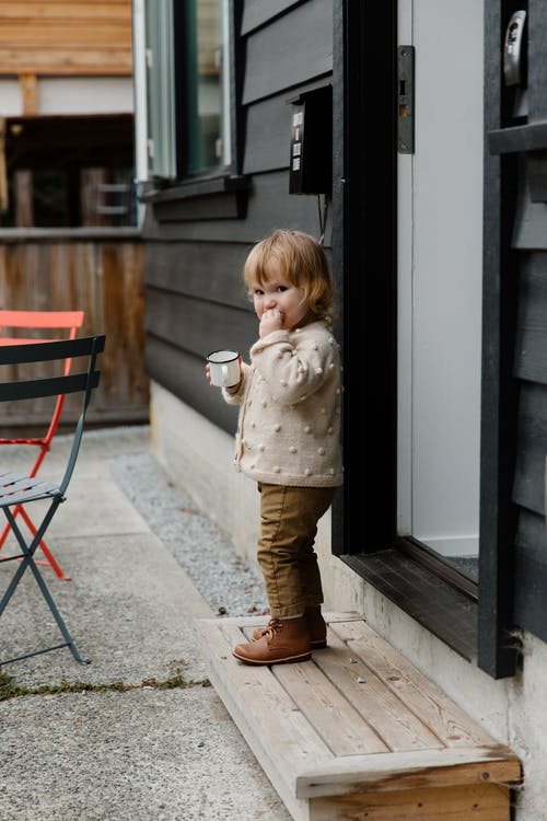 Little girl with cup of drink standing on stairs