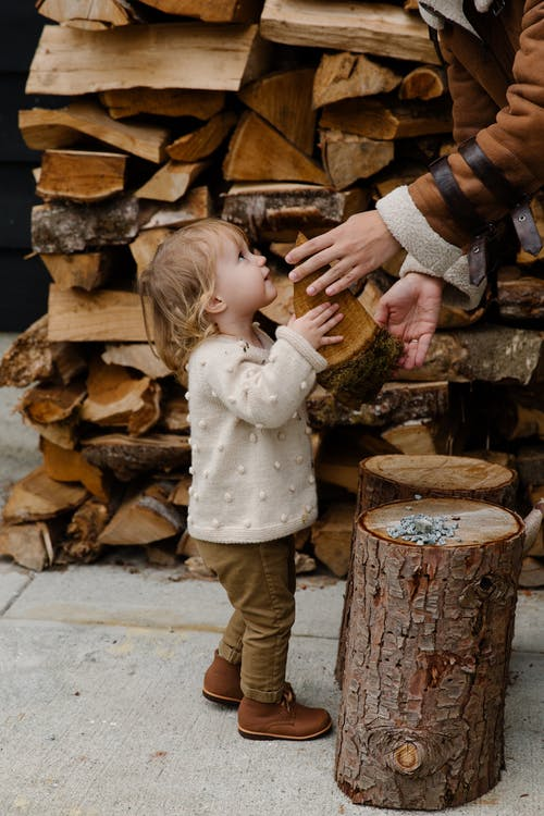 Little girl looking at father standing near firewood