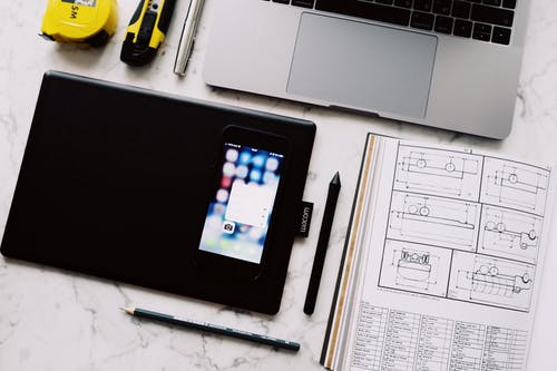 Modern workplace with gadgets and notebook on marble table