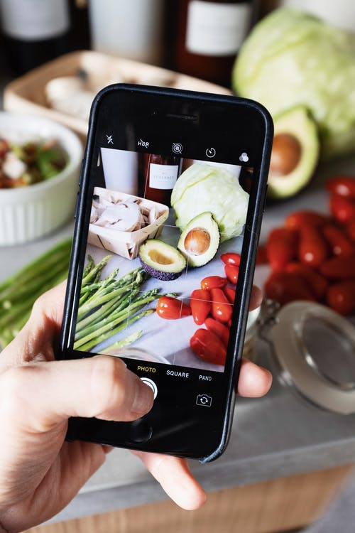 Anonymous crop person taking photo of food on table in kitchen