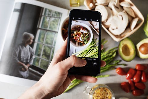 Anonymous crop person taking photo of food on smartphone at home