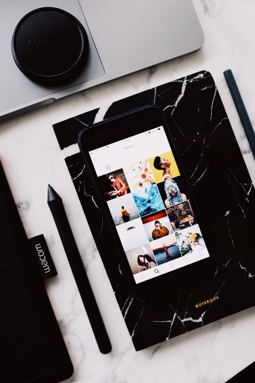 Notebook with smartphone showing photo gallery app on screen
