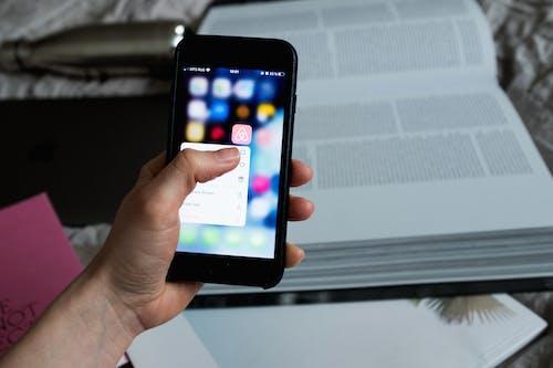 Crop unrecognizable person choosing application on smartphone