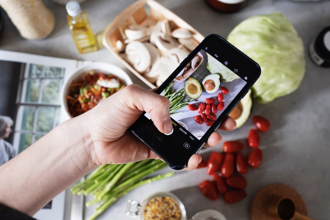 Person Holding Black Smartphone Taking Photos Of Food