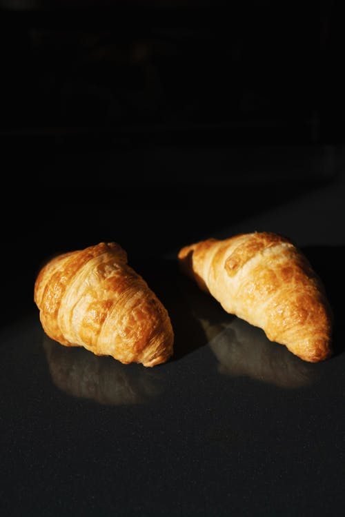 Pair of delicious fresh croissants on black glass background