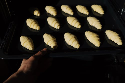 Person Holding Tray with Fresh Croissants