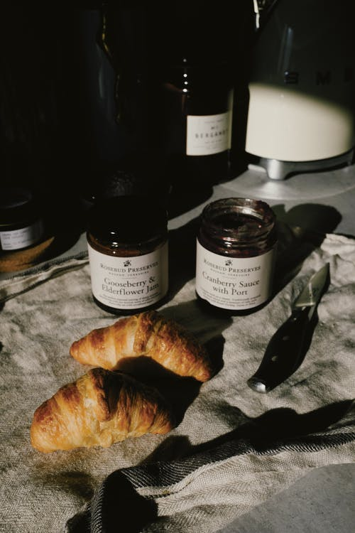 Delicious pair of fresh croissants with jars of jam and sauce on crumpled gray tissue