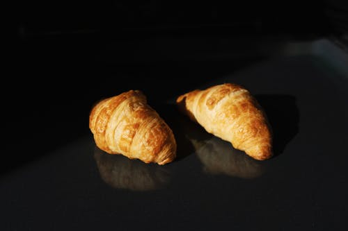 Pair of fresh yummy croissants on black glass surface