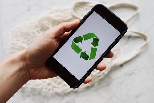 Crop unrecognizable person showing smartphone with recycle logo on screen
