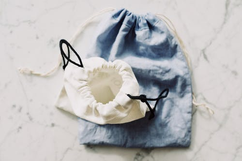 Top view of white and blue fabric eco friendly bags with drawstrings placed nearby on white marble table in light room