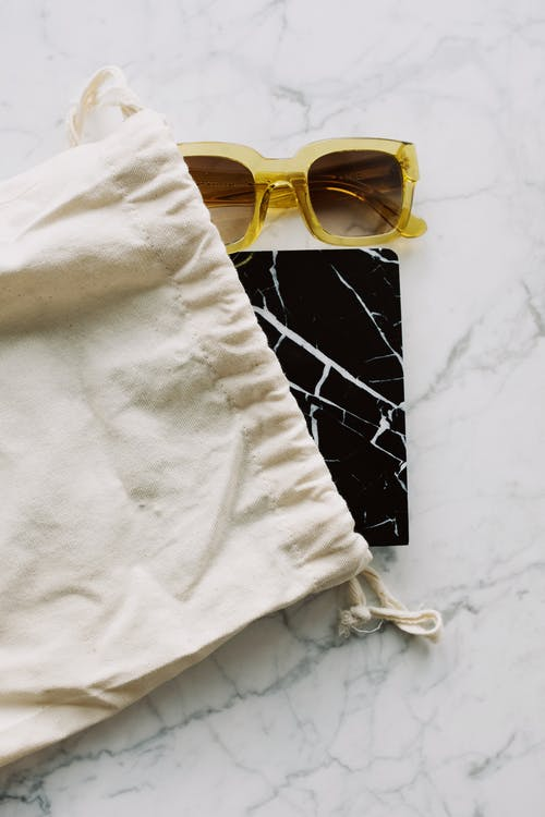 Sunglasses and notepad placed in white bag on marble table