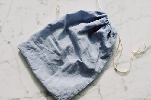 Empty textile blue bag with drawstrings placed on table in light room